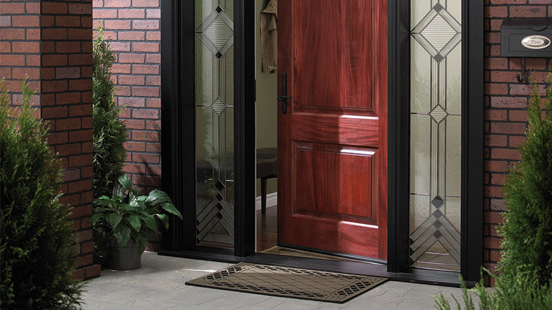 A modern reddish brown fibreglass front entry doors with black trim and custom sidelites.