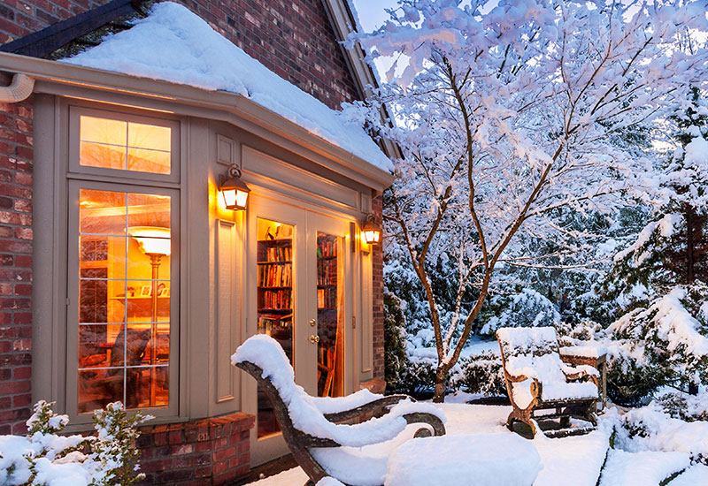 An exterior view of a snow covered home with a large patio door on a winter's evening.