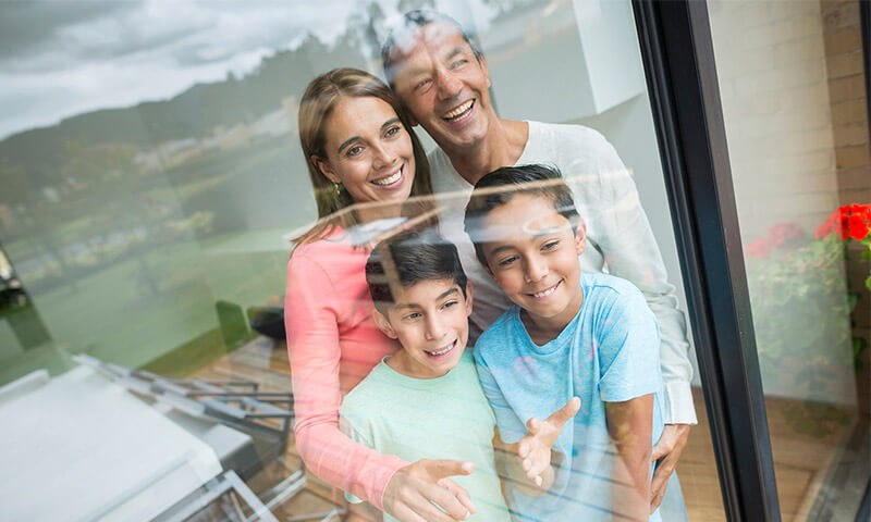 A family of four smiles while looking out of a large window.