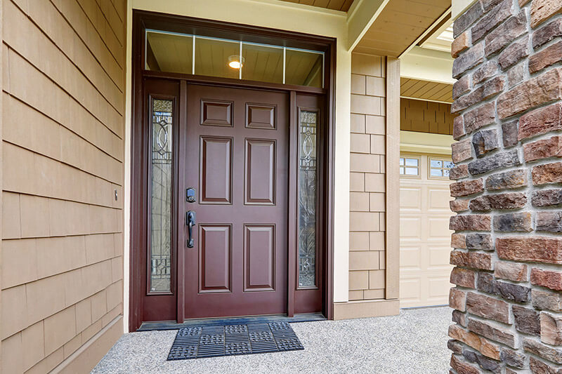 Mahogany steel entry door with modern, decorative glass sidelites and a square grille transom.