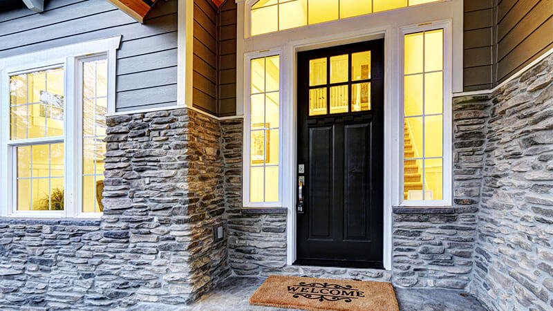 A modern black front door with rectangular glass insert.