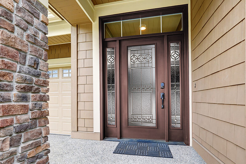 A modern, commercial brown steel entry door with full glass sidelites and custom, rectangular transom.