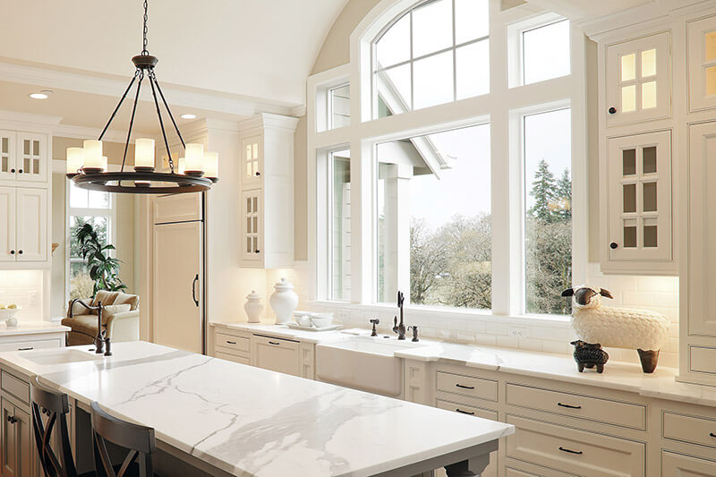Vinyl replacement windows above a kitchen sink in a modern, refinished kitchen.