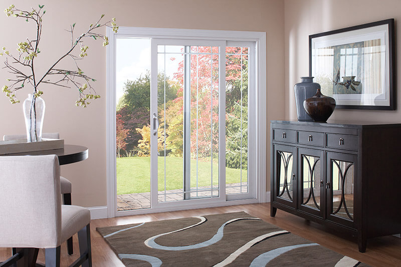 A sliding patio doors which leads from the backyard to a modern living room.
